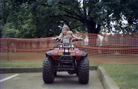 Girl and boy sitting on four wheeler