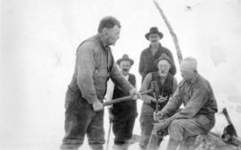 [Group photograph of men in snow, showing a man with a sledgehammer hitting a stake held by L.D. ...