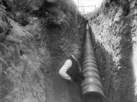 [A man in the sewer trench on Wilson Road (41st Avenue) near Larch Street]