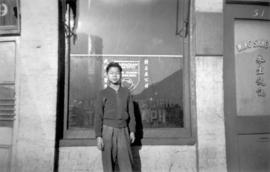 [Mel Yip standing in front of window of the Wing Sang Company Building at 51 East Pender Street]