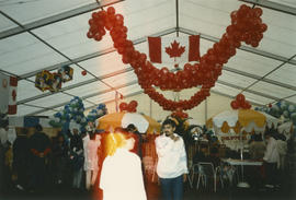 Man under Canadian flag and decorative balloons inside the Heritage Showcase tent