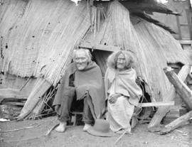 British Columbia Indians [seated in front of rough shelter]