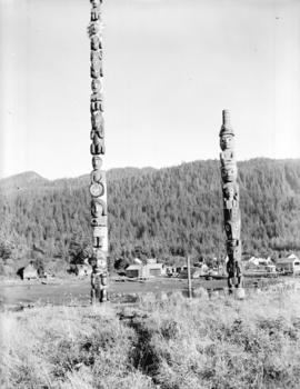 [View of totem poles with the town of Wrangell, Alaska in the background]