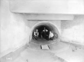 [Men in a sewer tunnel at China Creek]