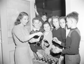 [Woman opening bottles of Coca-Cola to give to waiting children]