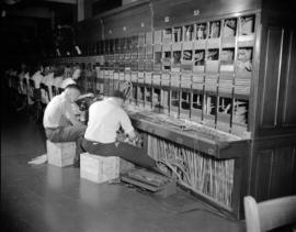 [B.C. Telephone technicians rewiring telephone switchboard system]