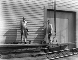 [Two men painting a Vancouver wharf]