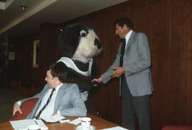 Tillicum shaking hands with a Centennial Committee member in meeting room at Vancouver City Hall