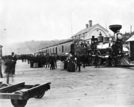 [Men and women gathered at platform next to C.P.R. locomotive 371]
