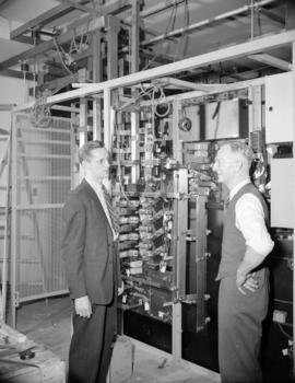 [B.C. Telephone personnel talking by new telephone switches]