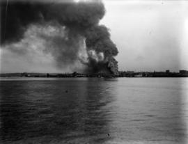 [View from the water of] fire at New England dock