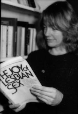Woman holds book 'The Joy of Lesbian Sex'