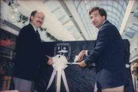 Mike Harcourt and unidentified man cut ribbon on display case