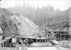 [Two men standing on partially completed wharf at construction site for Buntzen Lake Power Plant ...