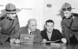[Sergeant E. Scott, Corporal M.J. Olsen, Major J.S. Matthews and Thomas Howarth study copies of &...
