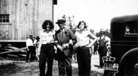 L.D. Taylor [standing with two women wearing trousers]
