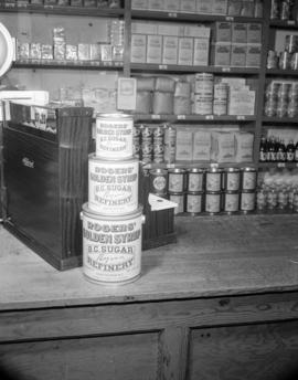 [Display of Rogers' Golden Syrup by a cash register]