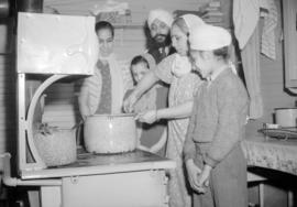 [Sikh family standing around a stove]