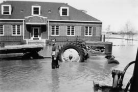 Dick Neufeld [standing in water with tractor]
