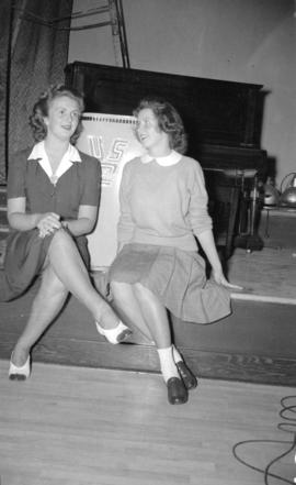 [Two women sitting on the stage at the Burrard Servicemen's Centre, 636 Burrard Street]