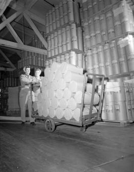 [Two women pushing a handcart loaded with paper] rolls [at] Pacific Mills