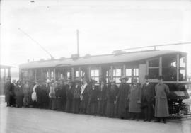 [Men and women assembled outside stepless streetcar before trial run]