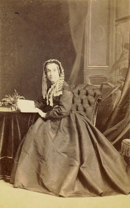 [Studio portrait of older woman in lace cap, seated at a table]