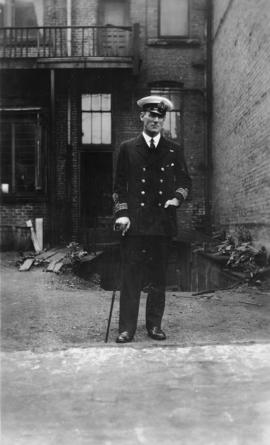 Capt. B.L. Johnson standing at back of brick building