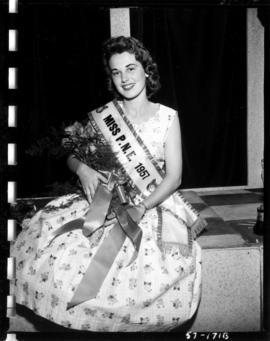 Carol Lucas, winner of Miss P.N.E. 1957, posing with flowers