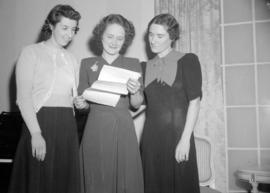 [Portrait of three women reading a document]