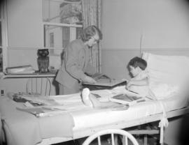 [Women from the Junior Leage playing with a young boy on a hospital ward]
