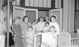 [Zazu Pitts with nurses and children in a hospital ward]