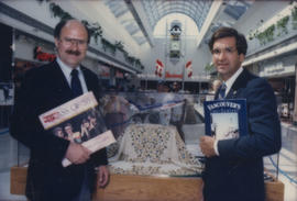 Mike Harcourt and unidentified man hold up books in front of display case