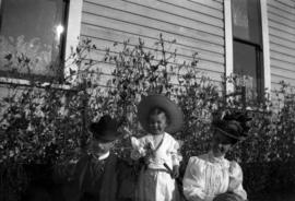 [L.D., Theodore and Annie Louise Taylor sitting in yard of their home at Willow Street and 8th Av...