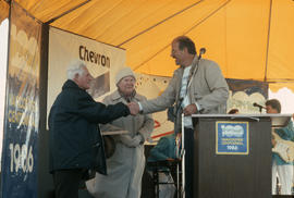 Mike Harcourt shaking hands with unidentified man and woman on stage at Polar Bear Swim