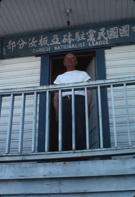 Man standing on the balcony of the Chinese Nationalist League Building in Nanaimo, B.C.