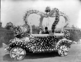 [Brown Bros.' open car decorated with crown motif in roses]
