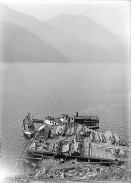 [Boats near dock piled with lumber for construction of Buntzen Lake Power Plant number one]