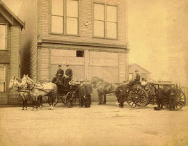 [Firefighters with engines in front of fire station]