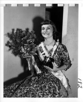 Joan Greenwood, winner of Miss P.N.E. 1956, posing with flowers and trophy