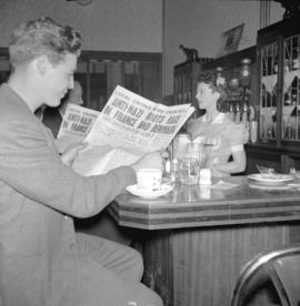 Reading [News Herald at a lunch counter]