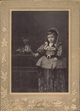 Portrait of small girl in checked dress, with Chihuahua beside her