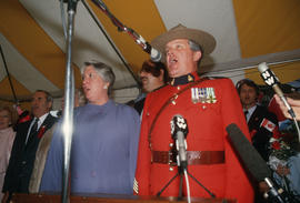 Pat Carney, Mike Harcourt and Mountie singing at the Centennial Commission's Canada Day celebration