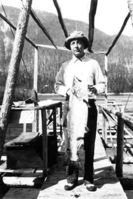 [Man posing with freshly caught salmon, Stuart Island, B.C.]