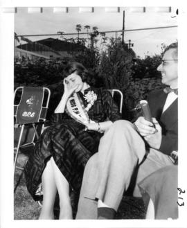 Miss P.N.E., Joan Greenwood, sitting in chair in B.C. Electric Garden and Information Centre