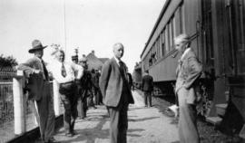 [L.D. Taylor with other men standing alongside a train]