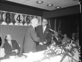 T.R. Fyfe passing gavel to the new P.N.E. president, H.W. Mullholland at P.N.E. meeting