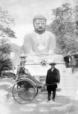 [Man with woman in rickshaw in front of large Buddha sculpture]