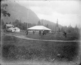 [Men and women riding bicycles near cottages at Harrison Hot Springs]