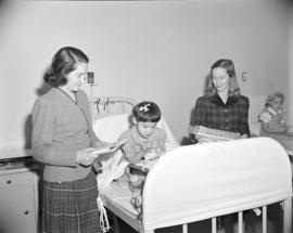 [Child playing with toys in bed while two women watch, possibly taken at a children's home o...